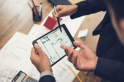 Construction IT Services - Man holding tablet and working with blueprints
